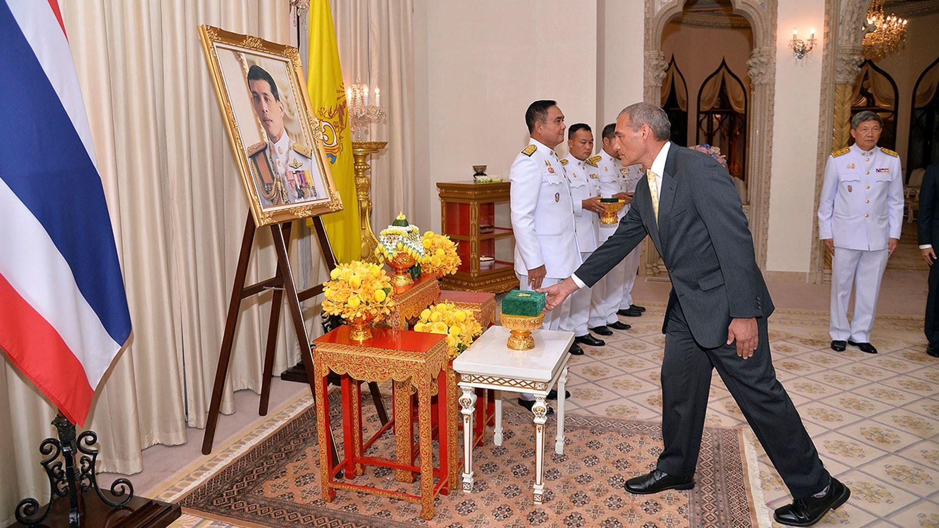 در این عکس که توسط دفتر سخنگوی دولت منتشر شده، کریگ چلن، عضو استرالیایی تیم نجات غار تایلند، عضو اعظم قابل تحسین از Direkgunabhorn در مقابل یک تصویری از شاه Maha Vajiralongkorn Bodindradebayavarangkun تایلند در مراسم تزیین سلطنتی در مجلس نمایندگان سلطنتی تایلند در بانکوک، تایلند، جمعه، 19 آوریل 2019.