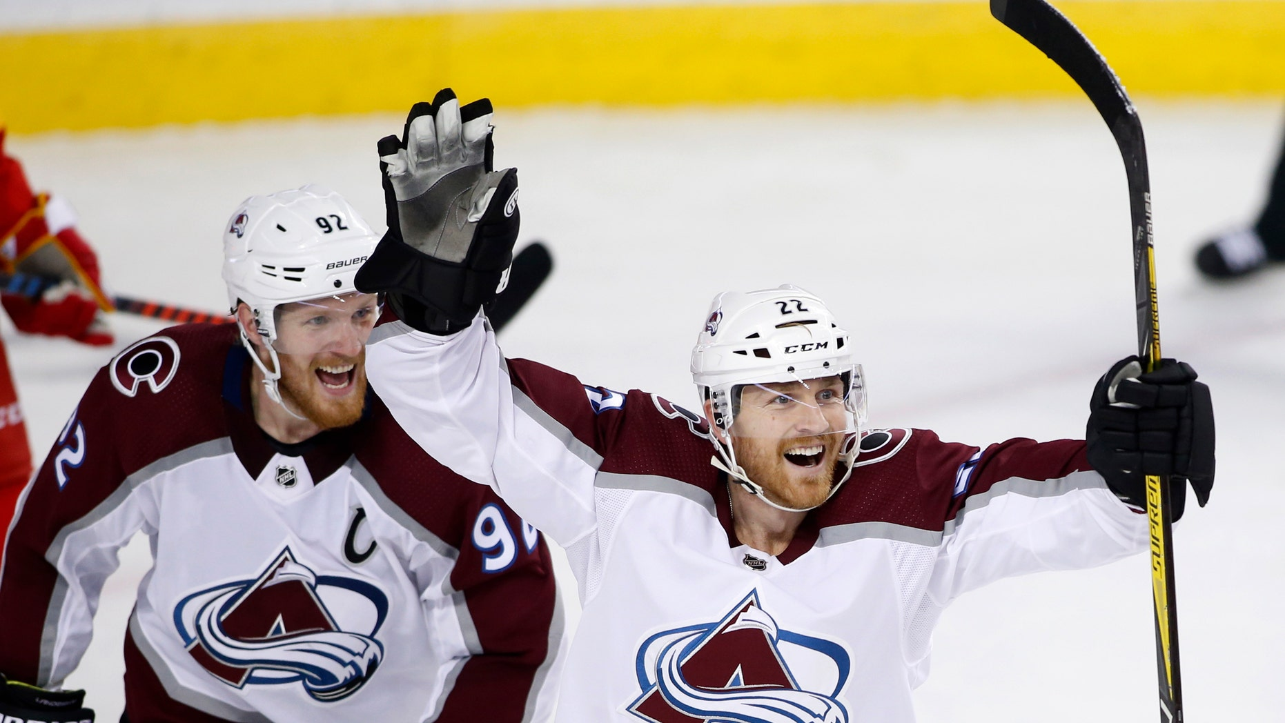 Colorado Avalanche center Colin Wilson (22) celebrates his goal against the Calgary Flames with teammate Gabriel Landeskog (92) during the second period of Game 5 of an NHL hockey first-round playoff series Friday, April 19, 2019, in Calgary, Alberta.