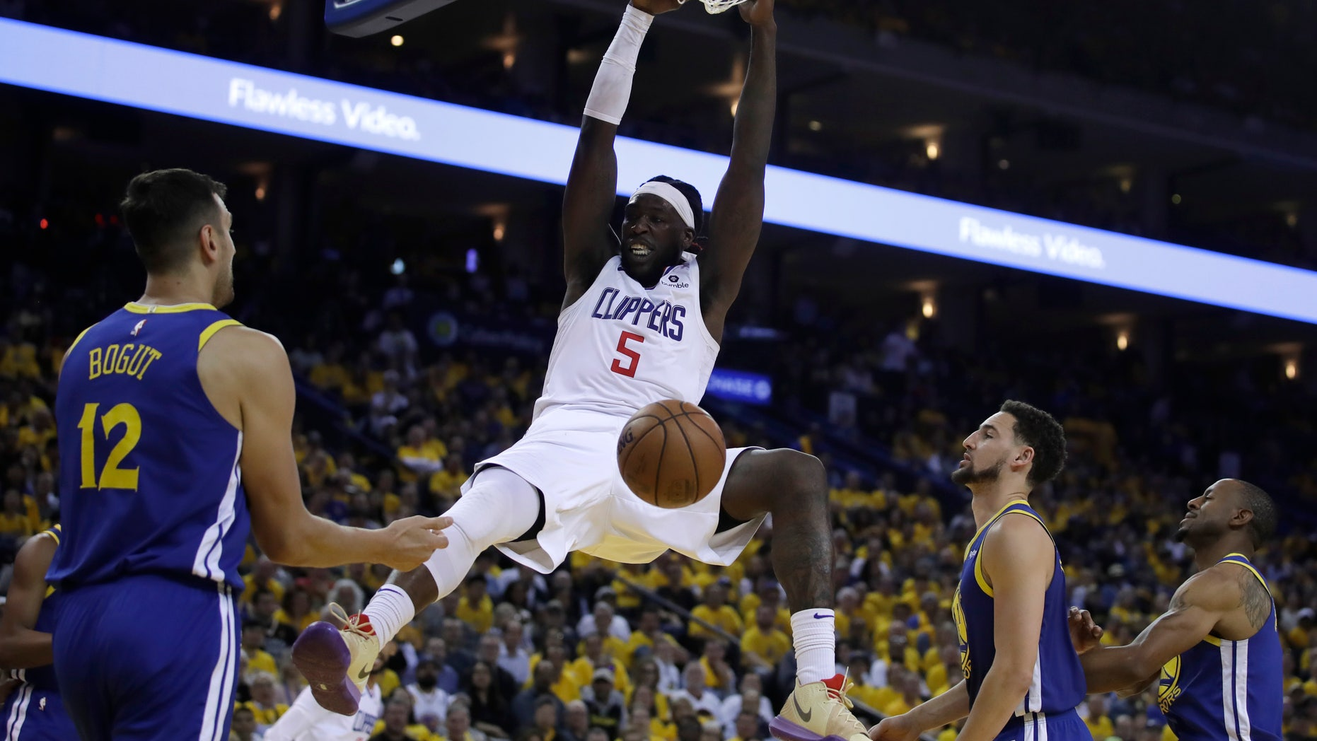 Los Angeles Clippers' Montrezl Harrell (5) scores as Golden State Warriors' Andrew Bogut (12), Klay Thompson, second from right, and Andre Iguodala watch during the second half in Game 5 of a first-round NBA basketball playoff series, Wednesday, April 24, 2019, in Oakland, Calif.