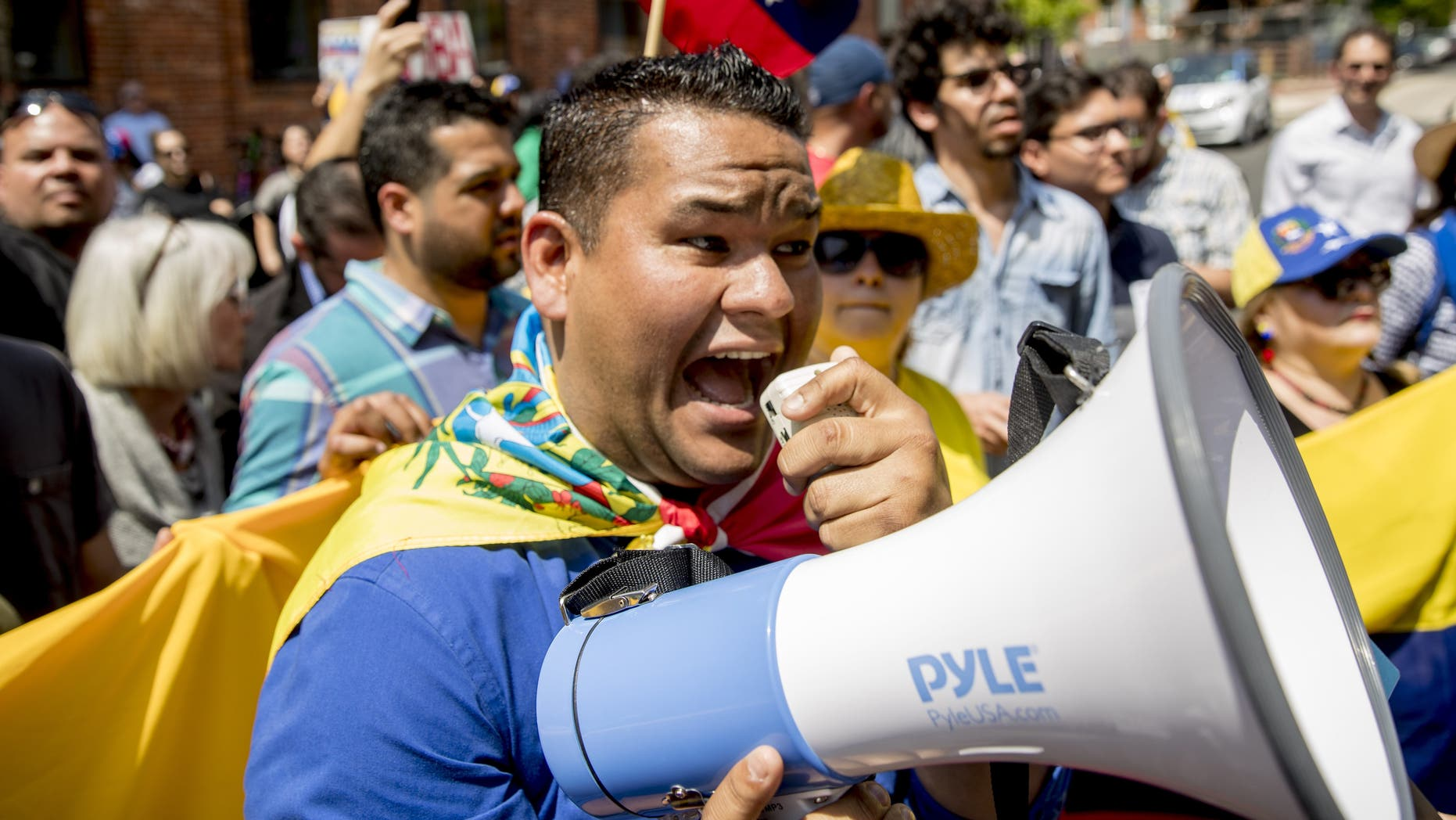 Supporters of interim government opposition leader Juan Guaido yell chants toward pro-Nicolas Maduro supporters as they rally outside of the Venezuelan Embassy in Washington, Tuesday, April 30, 2019. (AP Photo/Andrew Harnik)
