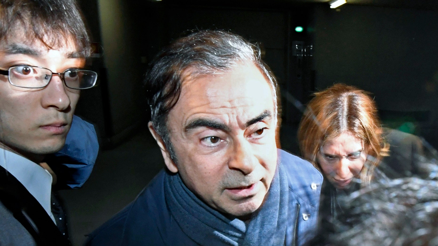 Former Nissan Chairman Carlos Ghosn, center, leaves his lawyer's office in Tokyo Wednesday. (Sadayuki Goto/Kyodo News via AP, File)