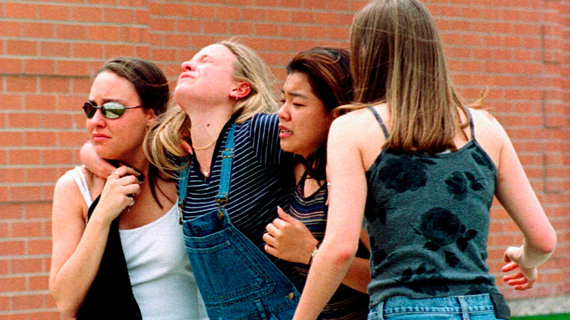 FILE - In this April 20, 1999, file photo, women head to a library near Columbine High School where students and faculty members were evacuated after two gunmen went on a shooting rampage in the school in the Denver suburb of Littleton, Colo. Twelve students and one teacher were killed in a murderous rampage at the school on April 20, 1999, by two students who killed themselves in the aftermath. (AP Photo/Kevin Higley, File)
