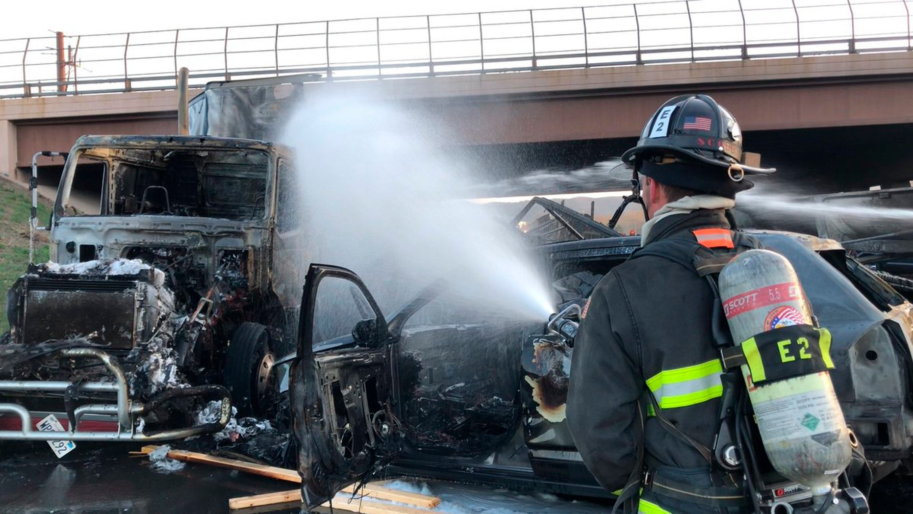 This Thursday, April 25, 2019 photo provided by West Metro Fire Rescue shows a firefighter working the scene of a deadly pileup involving over two dozen vehicles near Denver. A truck driver blamed for causing the deadly pileup has been arrested on vehicular homicide charges. Lakewood police spokesman Ty Countryman said Friday that there's no indication that drugs or alcohol played a role in the crash. (Ronda Scholting/West Metro Fire Rescue via AP)