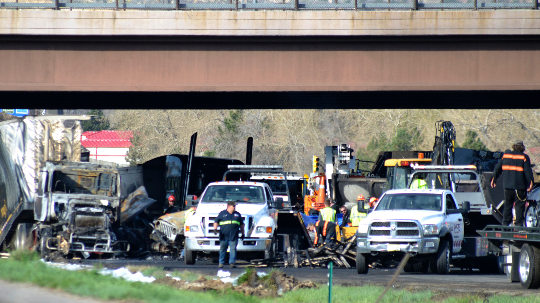 Authorities survey the scene of a fiery crash on I-70 near Colorado Mills Parkway that shut down the highway in both directions on Friday, April 26, 2019. Lakewood, Colo. A truck driver blamed for causing a deadly pileup involving over two dozen vehicles near Denver has been arrested on vehicular homicide charges. Lakewood police spokesman Ty Countryman said Friday that there's no indication that drugs or alcohol played a role in Thursday's crash. (AP Photo/Peter Banda)