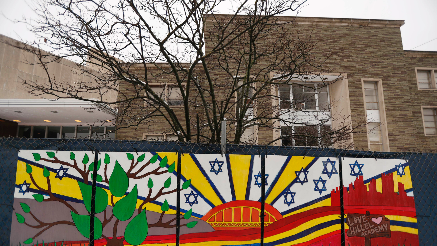 FILE--This file photo from Feb. 11, 2019 shows artwork on a fence around the Tree of Life Synagogue in Pittsburgh where 11 people were killed and seven others injured during an attack on in October of 2018. The synagogue is inviting young people worldwide to submit artwork in an art project called #HeartsTogether: The Art of Rebuilding. to cover more of the fencing that surrounds the still-shuttered building. They are looking for original, uplifting images and graphics to be printed on windscreens that will cover the temporary perimeter fencing. (AP Photo/Keith Srakocic, File)