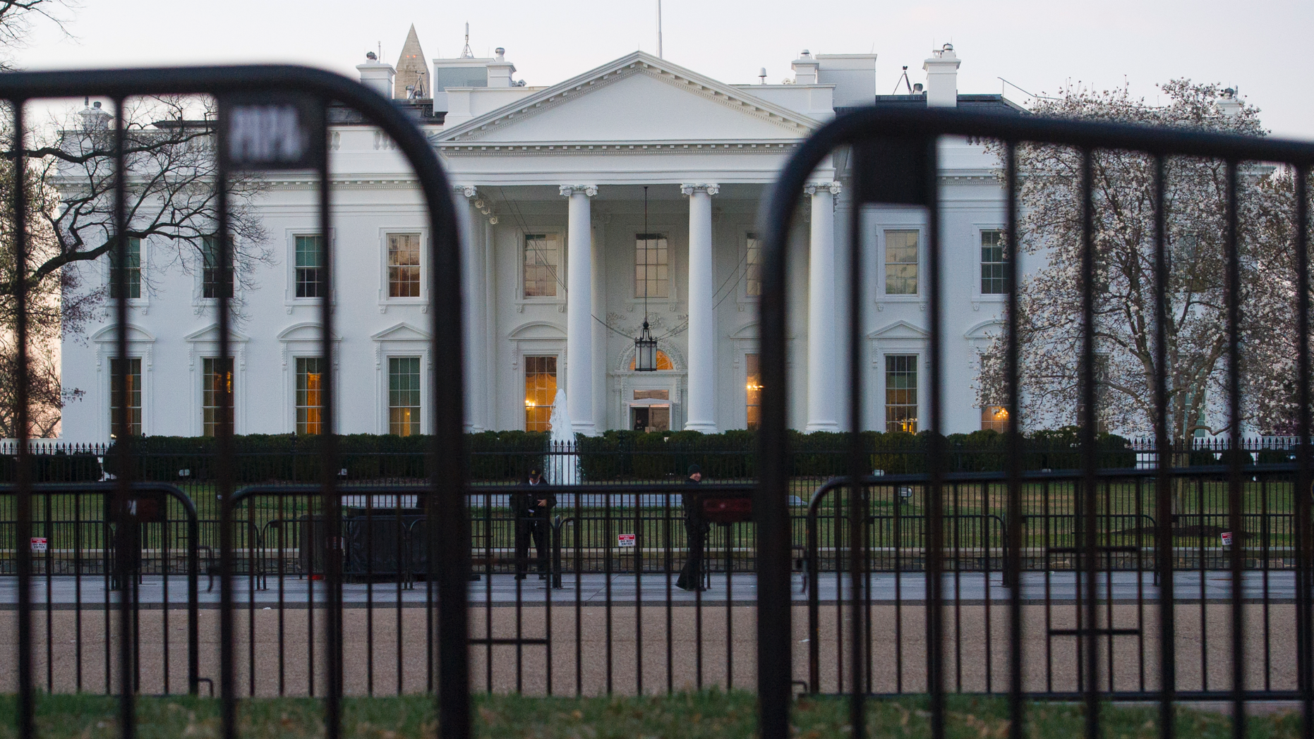 "In this March 24, 2019 photo, The White House is seen behind security barriers in Washington. A White House official turned whistleblower says dozens of people in President Donald Trump's administration were granted access to classified information despite ""disqualifying issues"" in their backgrounds including concerns about foreign influence, drug use and criminal conduct.  (AP Photo/Cliff Owen)"