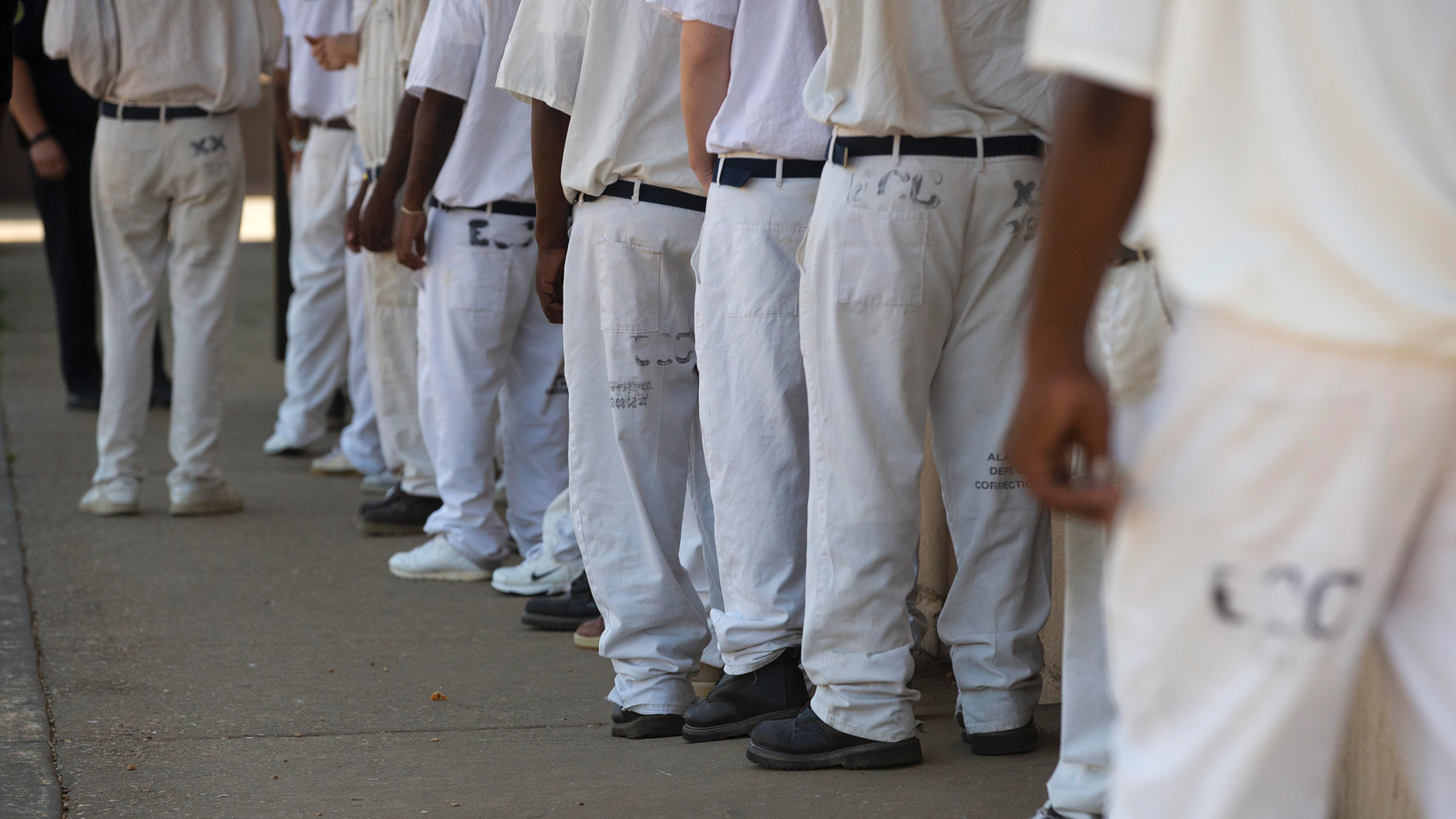 """FILE- In this June 18, 2015 file photo, prisoners stand in a crowded lunch line during a prison tour at Elmore Correctional Facility in Elmore, Ala. he Justice Department has determined that Alabama's prisons are violating the Constitution by failing to protect inmates from violence and sexual abuse and by housing them in unsafe and overcrowded facilities, according to a scathing report Wednesda, April 3, 2019, that described the problems as """"severe"""" and """"systemic."""". (AP Photo/Brynn Anderson)"""
