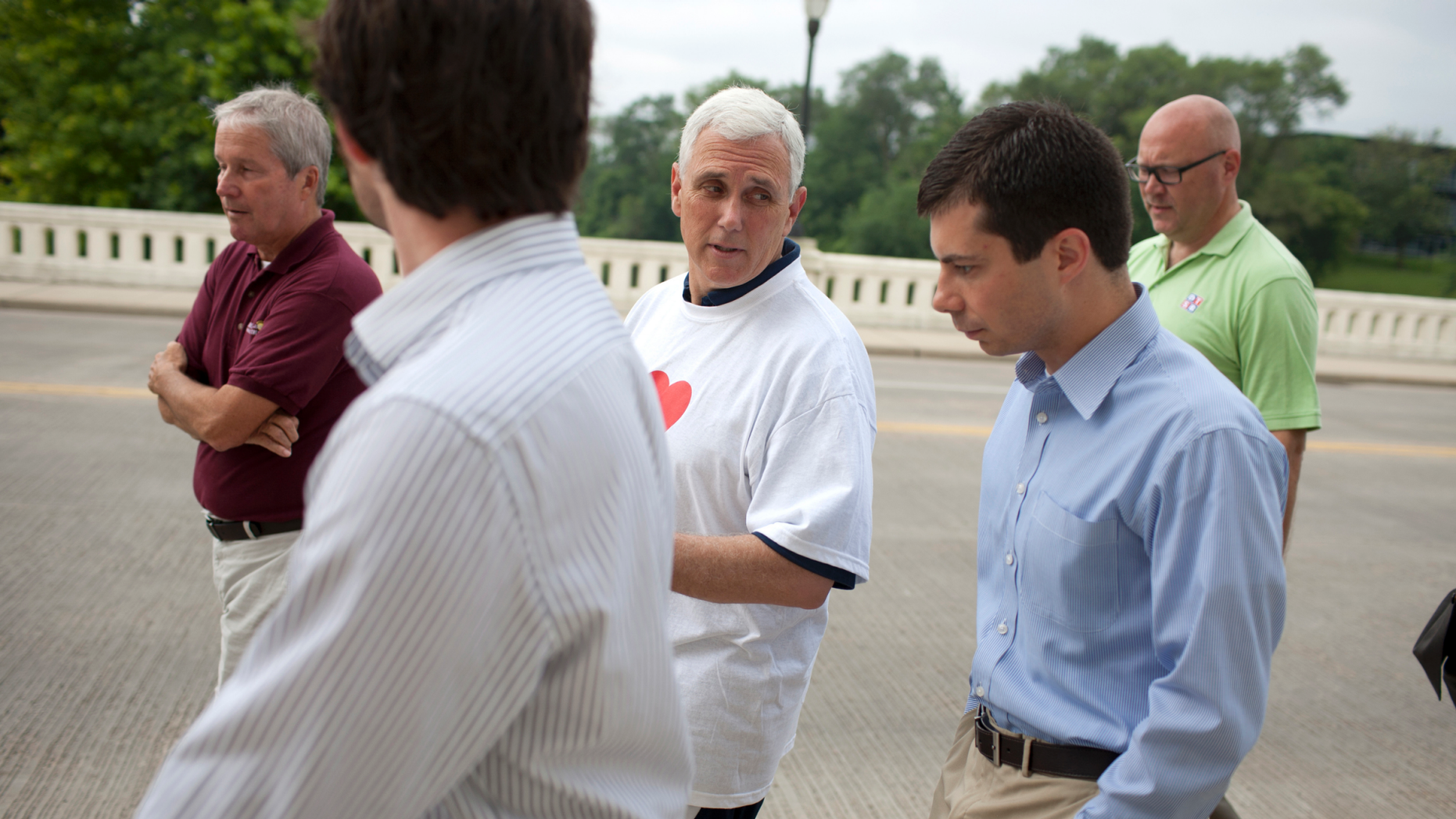 FILE - IN this July 3, 2013, file photo, then-Indiana Gov. Mike Pence, center, talks with South Bend mayor Pete Buttigieg, right, as they cross the Jefferson Boulevard bridge during a fitness walk along the St. Joseph River in downtown South Bend, Ind. Democratic presidential candidate Pete Buttigieg blasts Vice President Mike Pence's religious conservatism. But as the mayor of South Bend, Indiana, his tone toward the state's former governor was more muted. The two once had a cordial relationship. (AP Photo/South Bend Tribune, James Brosher)/South Bend Tribune via AP)