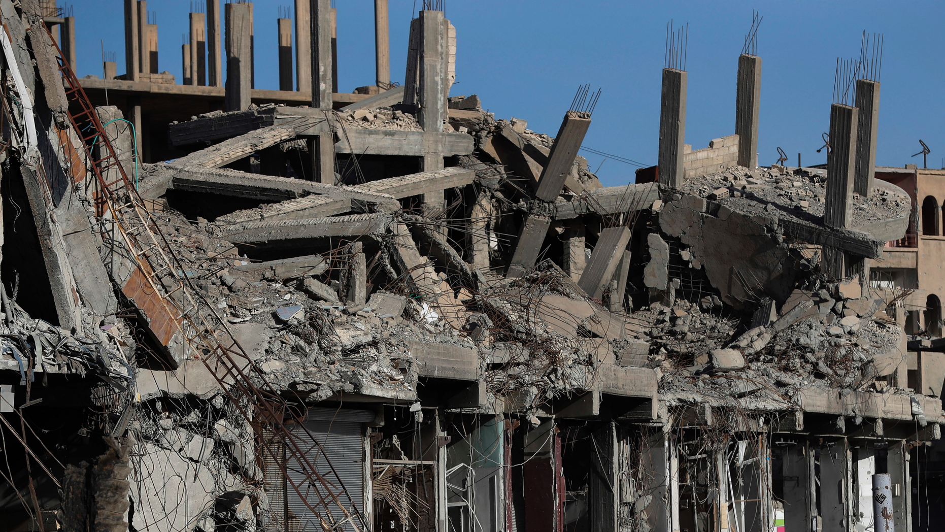 """FILE - In this April 5, 2018 file photo, destroyed buildings line a street damaged during fighting between U.S.-backed Syrian Democratic Forces fighters and Islamic State militants, in Raqqa, Syria. Amnesty International and Airwars, a London-based watchdog group, said Thursday, April 25, 2019, that the U.S.-led coalition killed more than 1,600 civilians in the northern Syria city of Raqqa during months of bombardment that liberated it from the Islamic State group. They said the toll came after the """"most comprehensive investigation into civilian deaths in a modern conflict."""" (AP Photo/Hussein Malla, File)"""