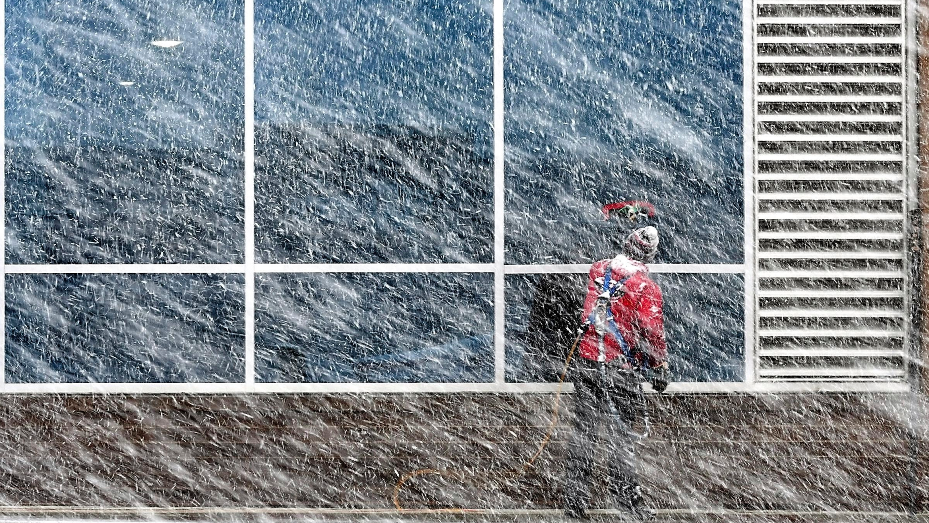 Xavier Castillo of Endres Window Cleaning finishes up a set of windows on the Profinium building in downtown Mankato, Minn., as snow falls Wednesday, Apr. 10, 2019. (Pat Christman/The Free Press via AP)