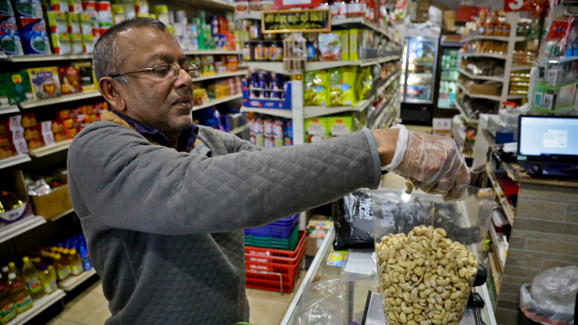 "Dhannitha Meemanage, from Sri Lanka, bags cashews in his family's grocery store, in New York's Staten Island's ""Little Sri Lanka"" community, Monday, April 22, 2019. Sri Lanka's abrupt shutdown of social media sites in the wake of the string of deadly Easter Sunday terror attacks has left worried friends and relatives in places like ""Little Sri Lanka"" in the dark. Meemanage, turned to old-fashioned means of getting news about loved ones after the attack, a landline phone. (AP Photo/Bebeto Matthews)"