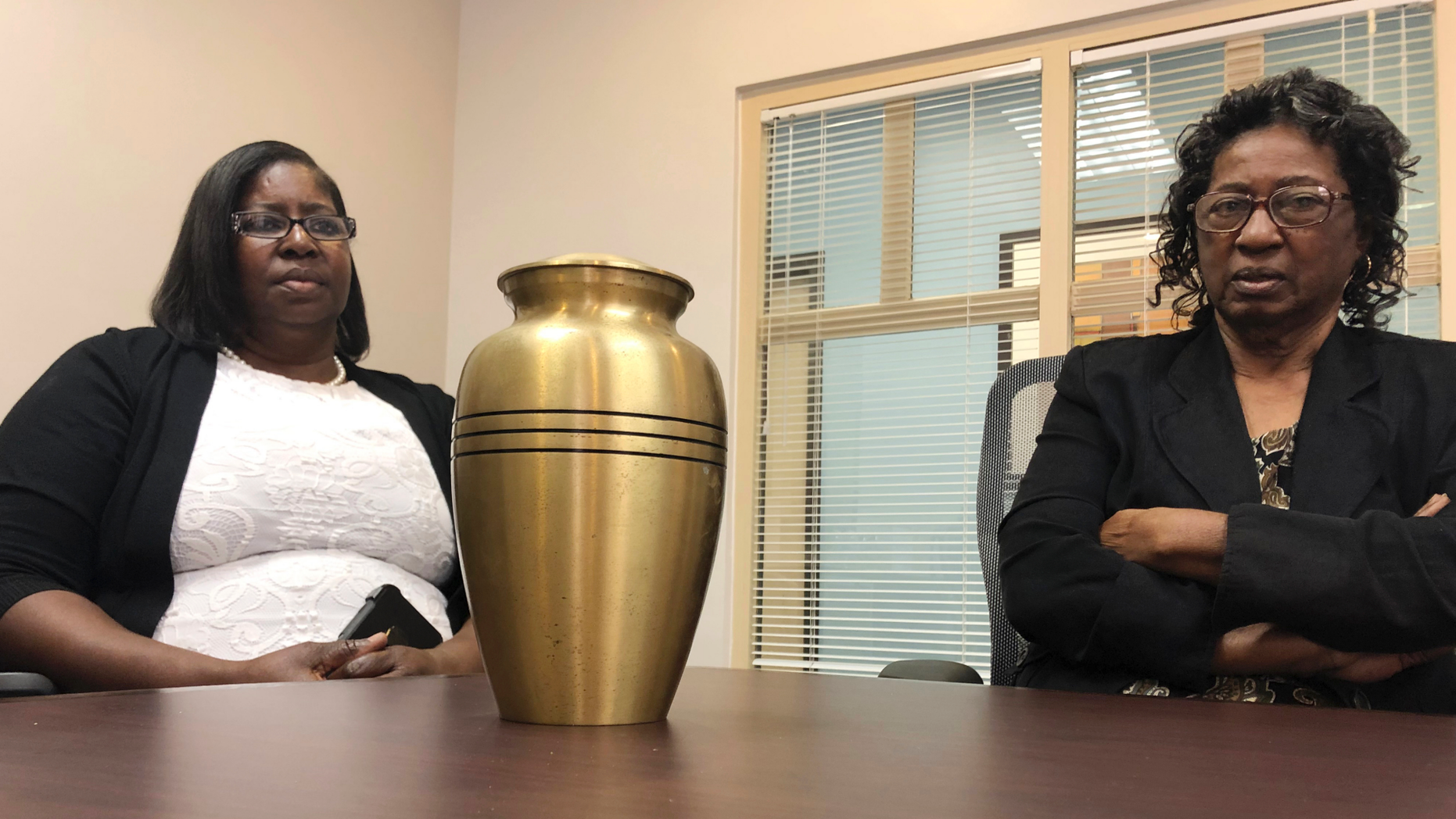Corene Nero, right, and her daughter Gloria Rolle speak at their attorneys office next to an urn with cremated remains, in Boca Raton, Fla., Tuesday, April 16, 2019. Robert Nero Sr., passed away in 2013 and was cremated by Taylor Smith funeral home. In March, West Palm Beach police Department found a box with Robert Nero's name on it filled with ashes. Now the family is demanding answers from the funeral home and want to return the remains they have to the right family. (AP Photo/Josh Repogle)