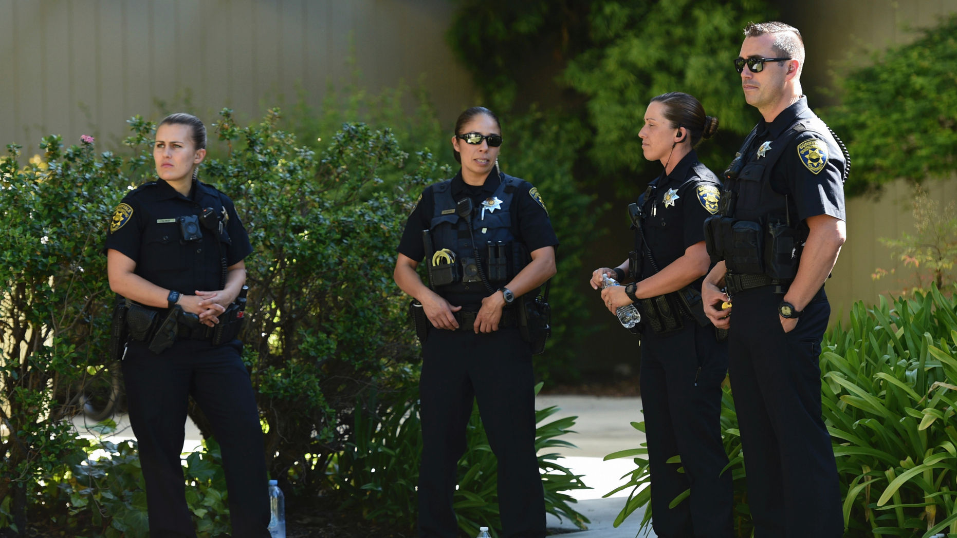 Police stand outside an apartment complex believed to be associated with a car crash suspect in Sunnyvale, Calif., on Wednesday, April 24, 2019. Investigators are working to determine the cause of the crash in Northern California that injured several pedestrians on Tuesday evening. Authorities say the driver of the car was taken into custody after he appeared to deliberately plow into the group. (AP Photo/Cody Glenn)