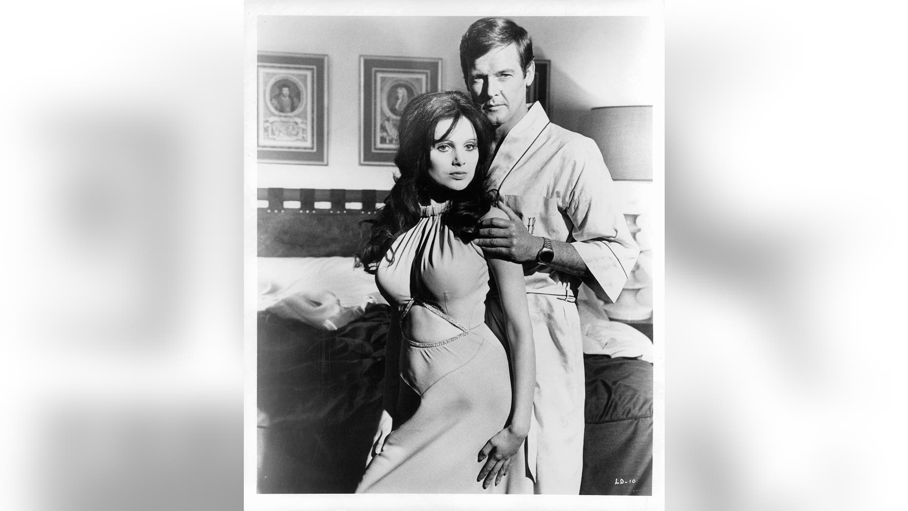 """Madeline Smith leaning against Roger Moore in a suggestive manner as he touches her arm in a scene from the film """"Live And Let Die,"""" 1973. —Photo by United Artist/Getty Images"""