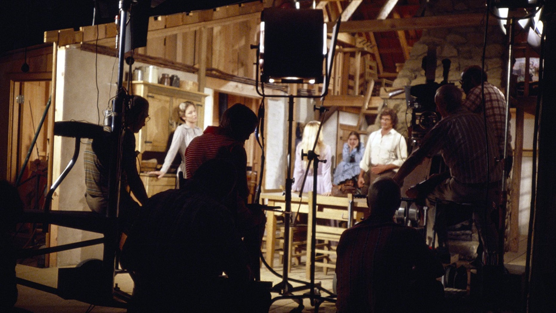 """The cast and crew of """"Little House on the Prairie"""" in a studio set."""