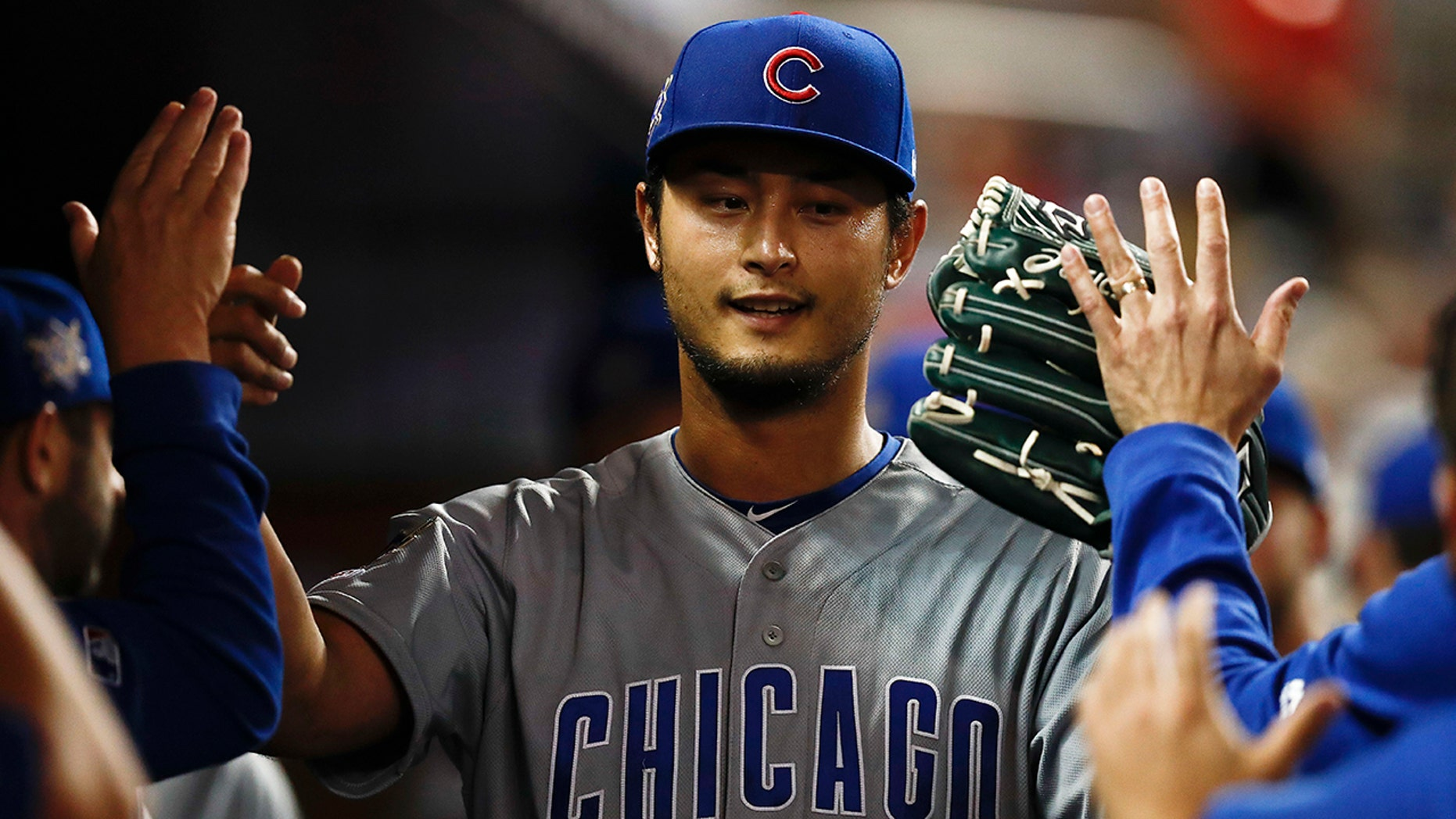 Chicago Cubs starting pitcher Yu Darvish high-fives teammates after being taken out of a baseball game during the seventh inning against the Miami Marlins, Monday, April 15, 2019, in Miami. (AP Photo/Brynn Anderson)