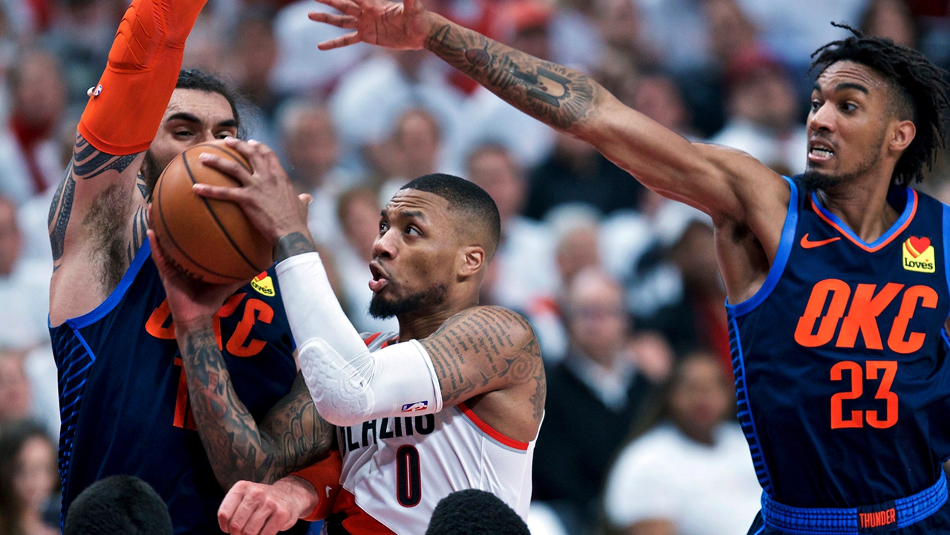 Portland Trail Blazers guard Damian Lillard, center, shoots between Oklahoma City Thunder center Steven Adams, left, and guard Terrance Ferguson, right, during the second half of Game 5 of an NBA basketball first-round playoff series, Tuesday, April 23, 2019, in Portland, Ore. The Trail Blazers won 118-115. (AP Photo/Craig Mitchelldyer)