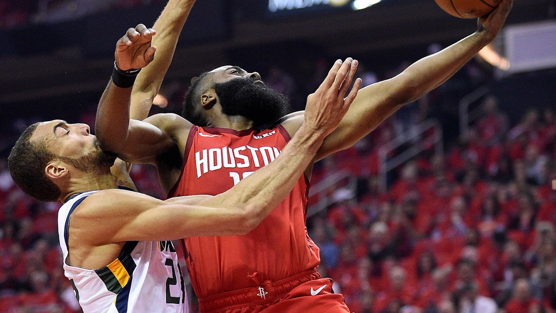 Houston Rockets guard James Harden, right, drives to the basket as Utah Jazz center Rudy Gobert defends during the first half of Game 1 of an NBA basketball first-round playoff series, Sunday, April 14, 2019, in Houston. (AP Photo/Eric Christian Smith)