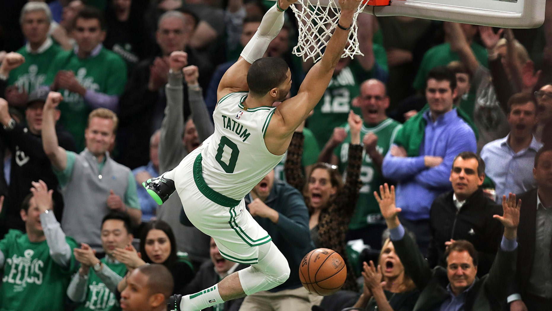 Boston Celtics forward Jayson Tatum (0) hangs on the rim after slamming a dunk against the Indiana Pacers in the final minute of the fourth quarter of Game 2 of an NBA basketball first-round playoff series, Wednesday, April 17, 2019, in Boston. The Celtics won 99-91. (AP Photo/Charles Krupa)