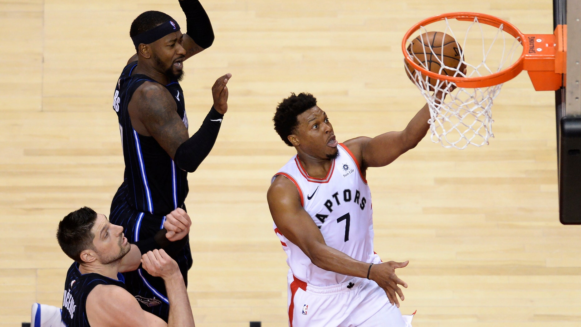 Toronto Raptors guard Kyle Lowry (7) scores past Orlando Magic center Nikola Vucevic (9) and guard Terrence Ross (31) during the second half of Game 2 of an NBA basketball first-round playoff series Tuesday, April 16, 2019, in Toronto. (Nathan Denette/The Canadian Press via AP)