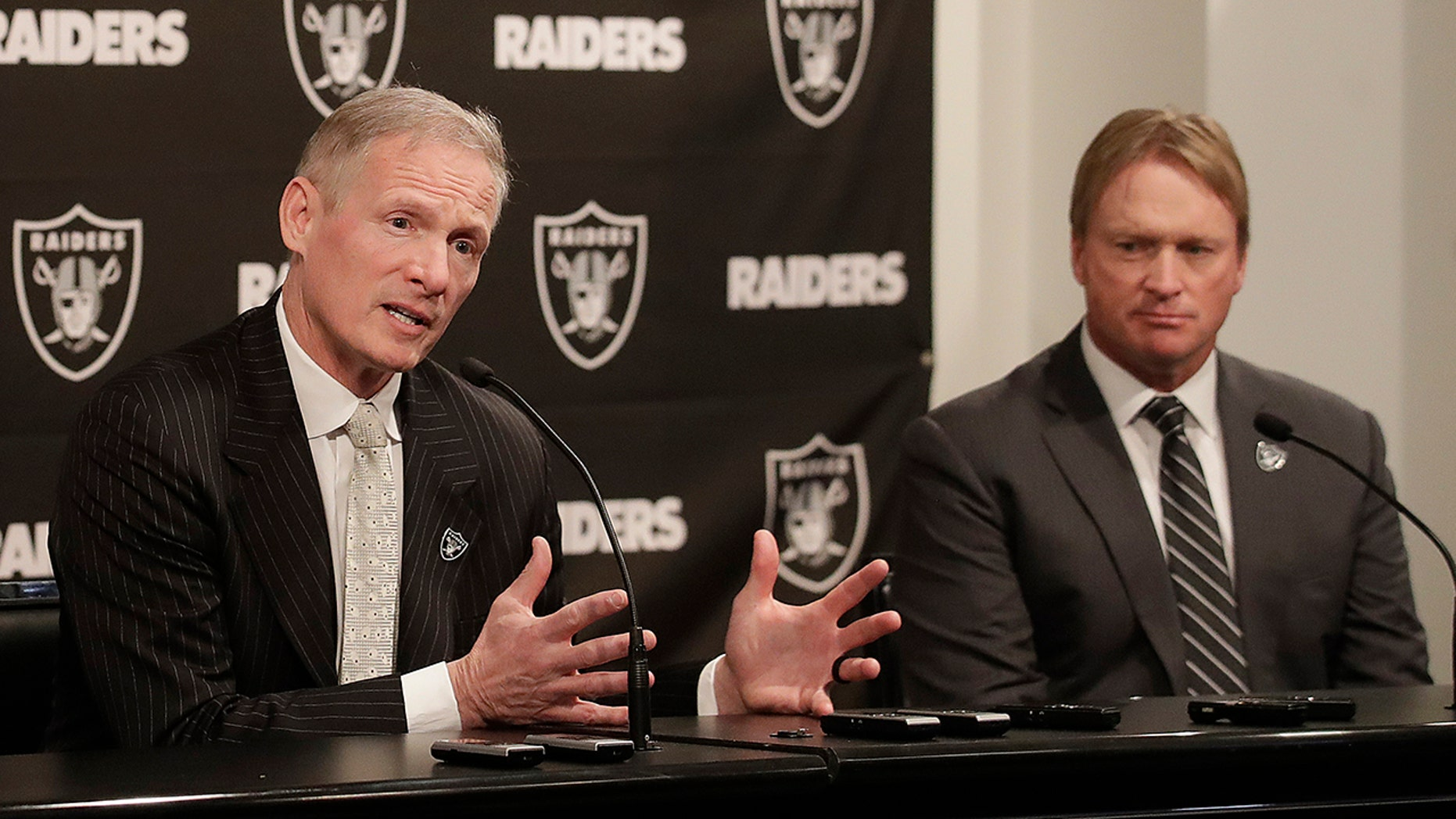 In this Dec. 31, 2018, file photo, Mike Mayock speaks as Oakland Raiders head coach Jon Gruden listens at a news conference announcing Mayock as the general manager at the team's headquarters in Oakland, Calif. (AP Photo/Jeff Chiu, File)