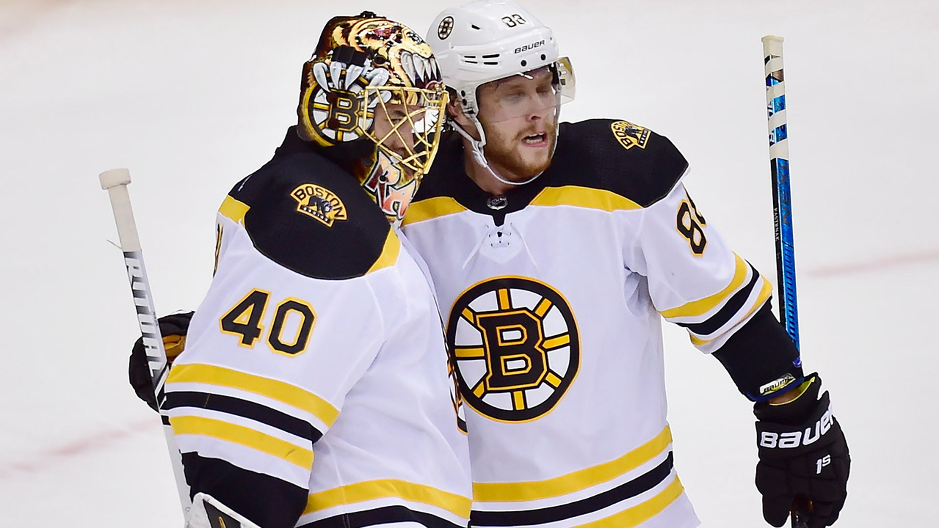 Boston Bruins goaltender Tuukka Rask (40) and teammate David Pastrnak (88) celebrate defeating the Toronto Maple Leafs after Game 4 of an NHL hockey first-round playoff series Wednesday, April 17, 2019, in Toronto. (Frank Gunn/The Canadian Press via AP)