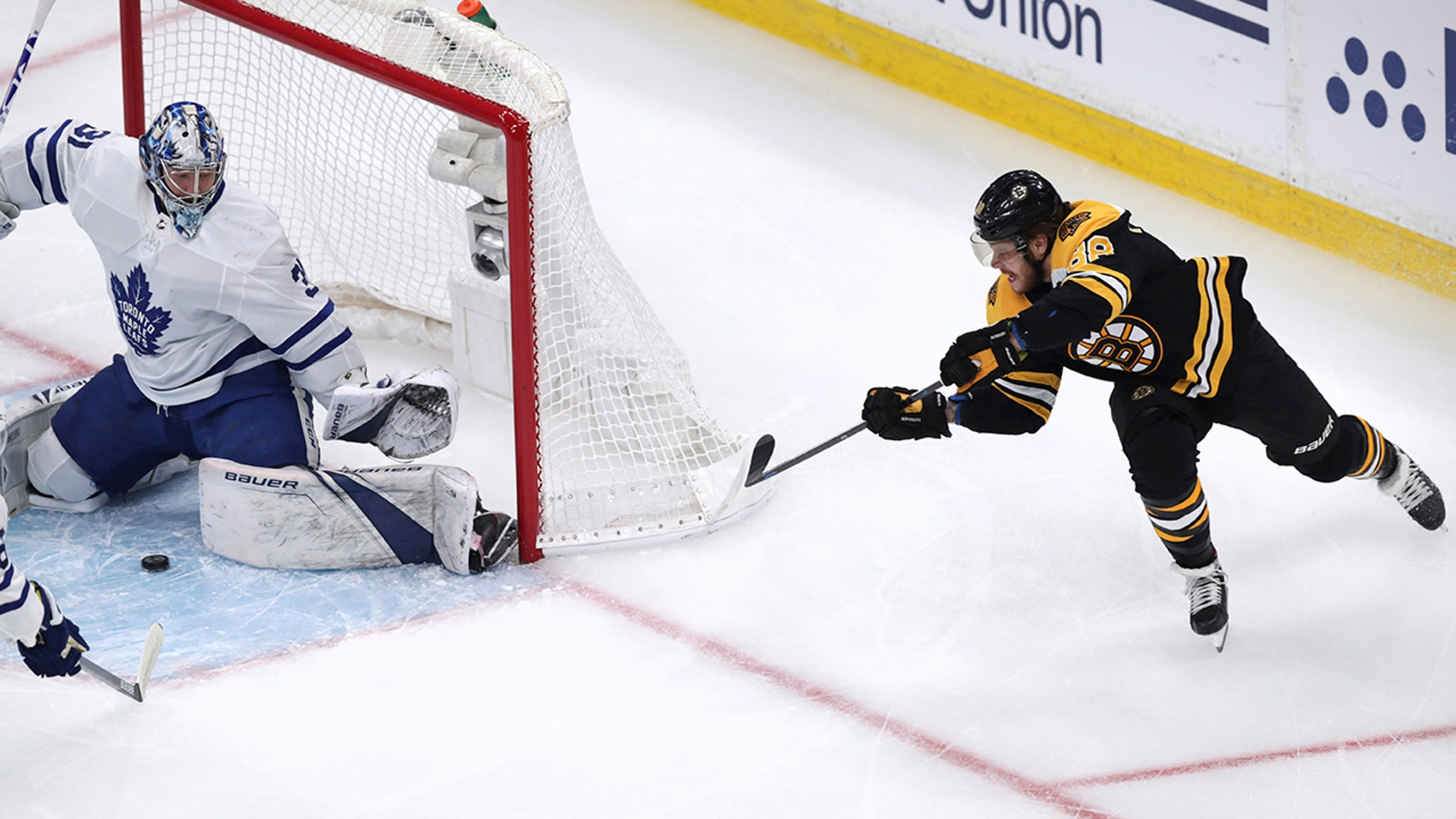 Boston Bruins right wing David Pastrnak, right, fires the puck in front of Toronto Maple Leafs goaltender Frederik Andersen (31) during the first period of Game 7 of an NHL hockey first-round playoff series, Tuesday, April 23, 2019, in Boston. (AP Photo/Charles Krupa)