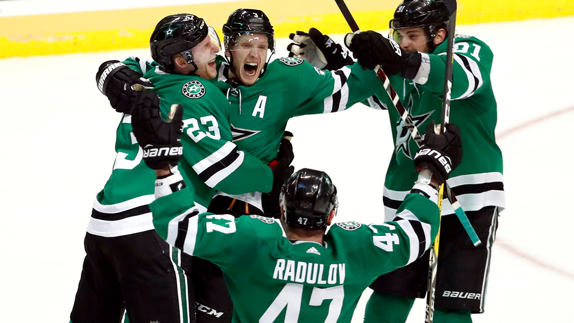 Dallas Stars' Esa Lindell (23), Alexander Radulov (47) and Tyler Seguin (91) celebrate with John Klingberg, center, who scored in overtime against the Nashville Predators in Game 6 of an NHL hockey first-round playoff series in Dallas, Monday, April 22, 2019. The Stars won 2-1 in overtime. (AP Photo/Tony Gutierrez)