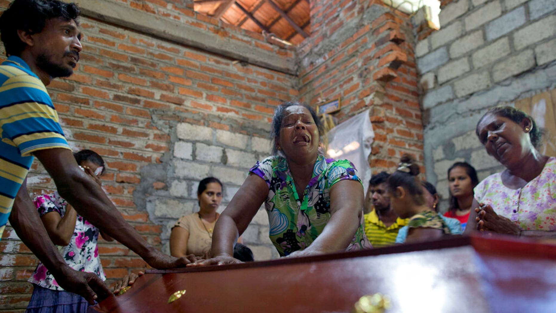 Lalitha, center, weeps over the coffin with the remains of 12-year old niece, Sneha Savindi, who was a victim of Easter Sunday bombing at St. Sebastian Church, after it returned home in Negombo, Sri Lanka, Monday, April 22, 2019. Easter Sunday bombings of churches, luxury hotels and other sites was Sri Lanka's deadliest violence since a devastating civil war in the South Asian island nation ended a decade ago. (AP Photo/Gemunu Amarasinghe)
