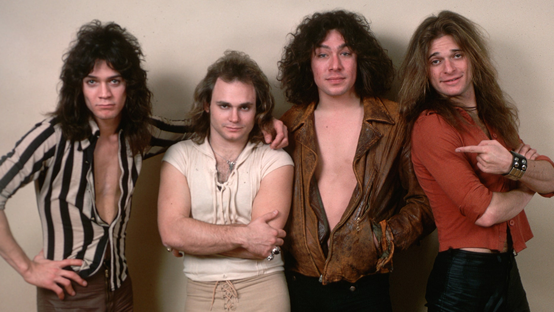 (Original Caption) : 1978- Picture shows the four members of the band Van Halen (left to right) Eddie Van Halen, Michael Anthony, Alex Van Halen and David Lee Roth. They are standing next to one-another in front of a white wall. (Photo by Lynn Goldsmith/Corbis/VCG via Getty Images)