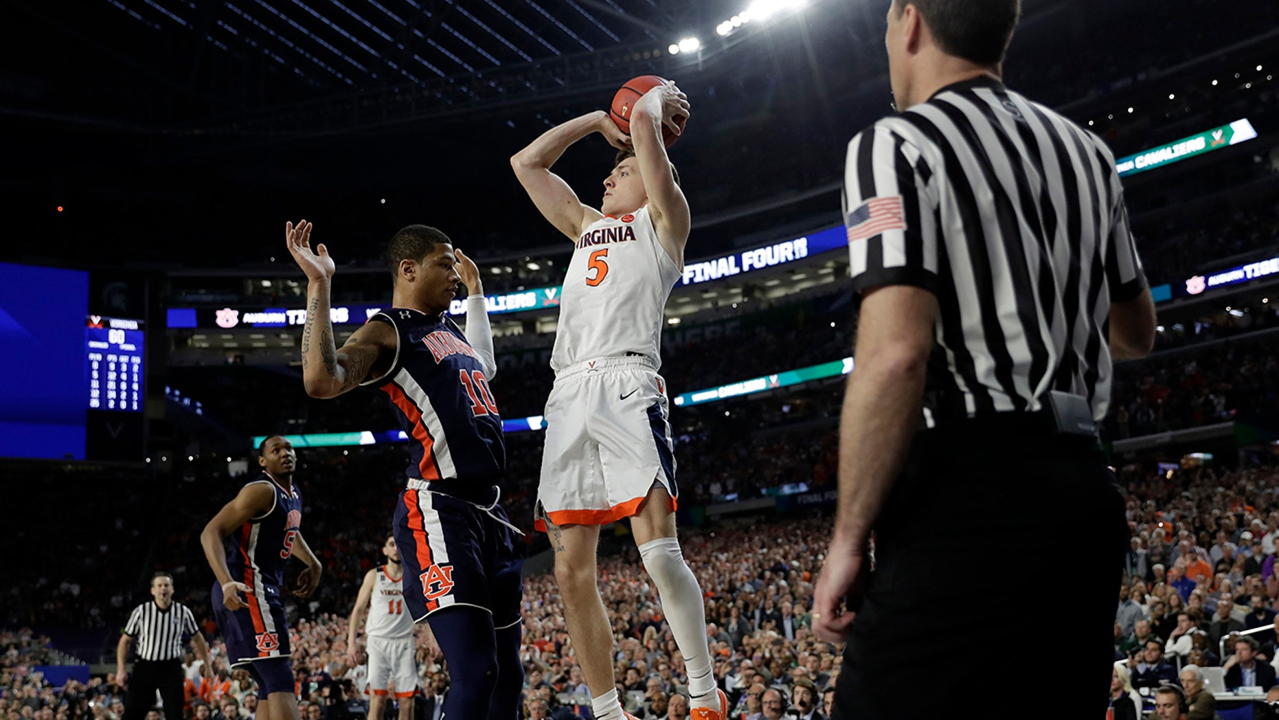 Virginia's Kyle Guy (5) takes a shot as Auburn's Samir Doughty (10) was called foul during the second half in the semifinals of the Final Four NCAA college basketball tournament, Saturday, April 6, 2019, in Minneapolis. (Associated Press)