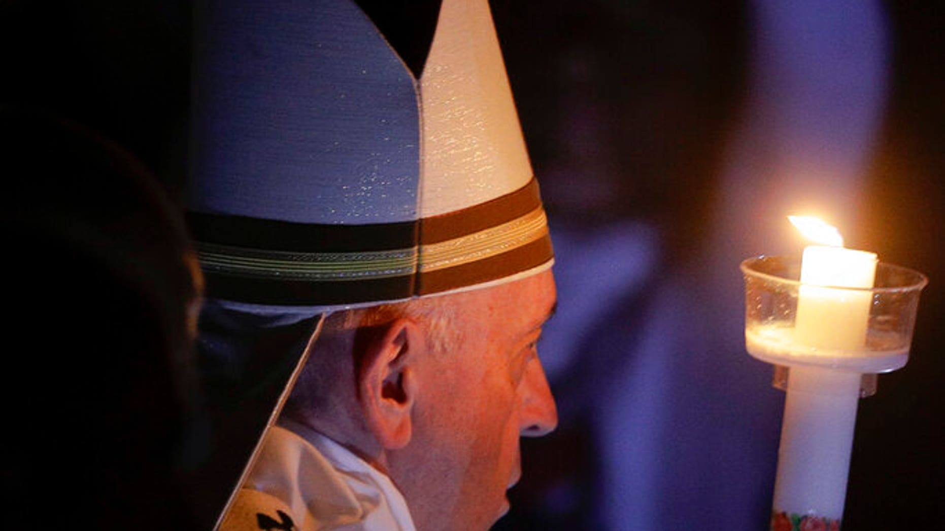 Pope Francis holds a candle as he presides over a solemn Easter vigil ceremony in St. Peter's Basilica at the Vatican, Saturday, April 21, 2019. (AP Photo/Gregorio Borgia)