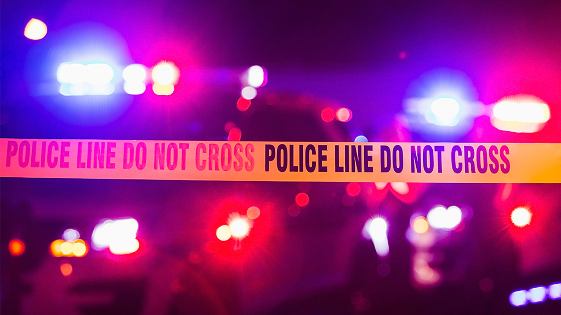 Accident or crime scene cordon tape, police line do not cross. It is nighttime, emergency lights of police cars flashing blue, red and white in the background