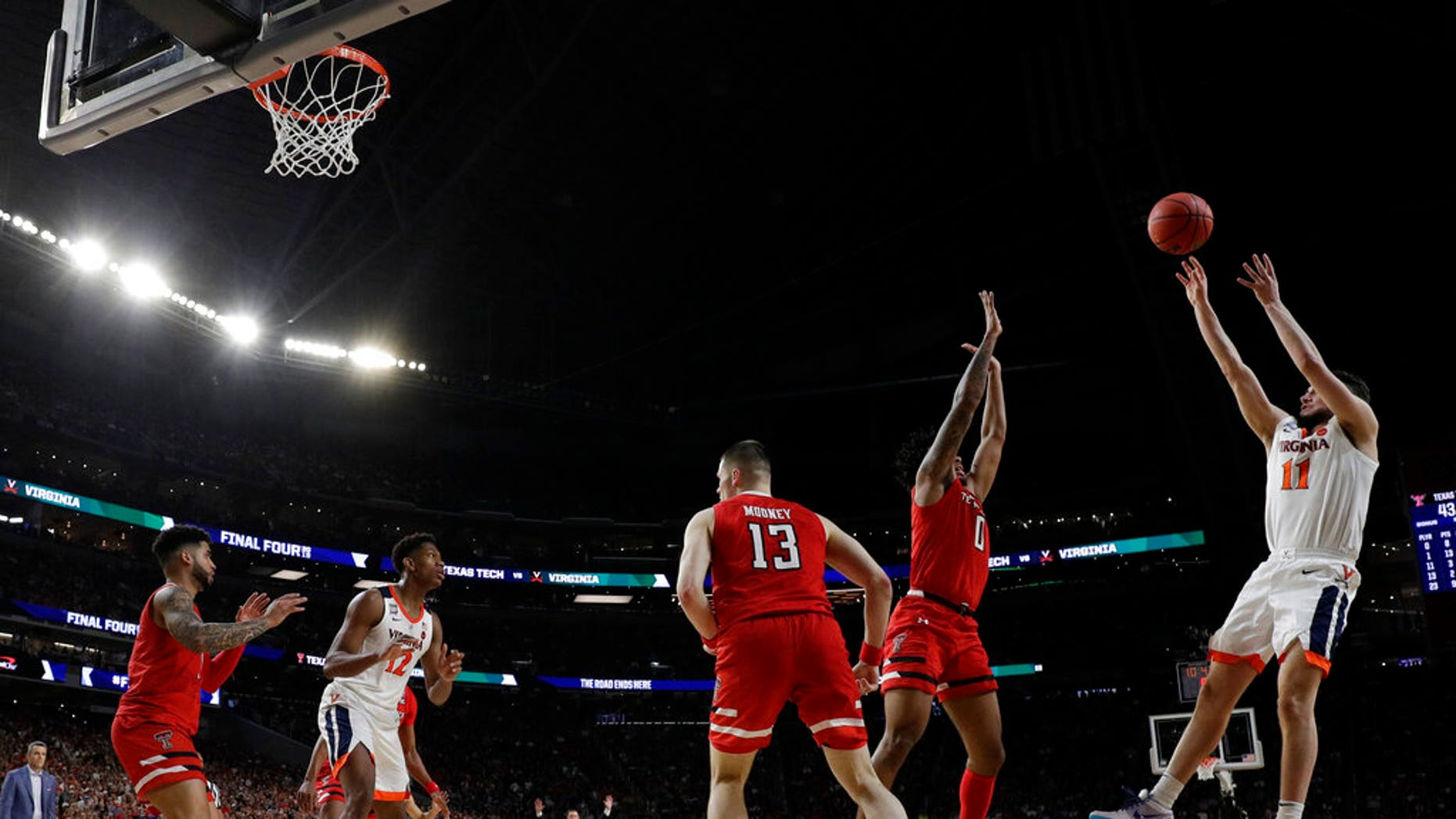 Virginia's Ty Jerome (11) makes a shot against Texas Tech's Kyler Edwards (0) during the second half in the championship of the Final Four NCAA college basketball tournament, Monday, April 8, 2019, in Minneapolis.