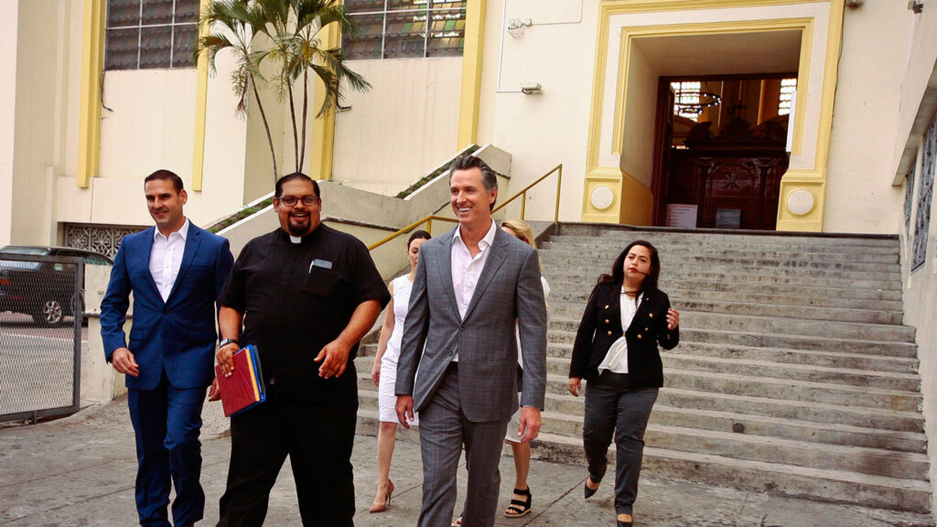 California Gov. Gavin Newsom, second from right, walks out with San Salvador Mayor Ernesto Muyshondtof, far left, after they visited the tomb of Archbishop Oscar Romero at Metropolitan Cathedral in San Salvador, El Salvador.