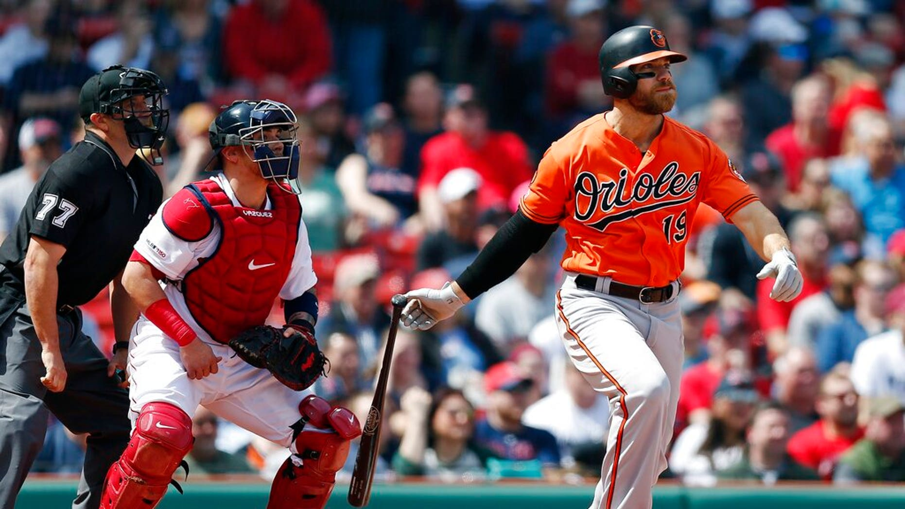 Chris Davis of Baltimore Orioles watches his single with two points ahead of Christian Vazquez of the Boston Red Sox in the first round of a baseball game in Boston on Saturday, April 13, 2019.