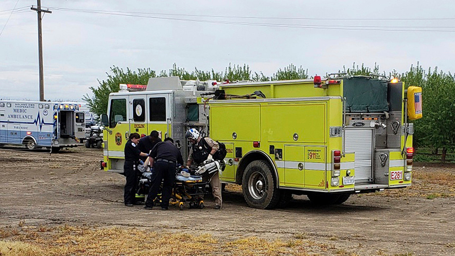 Fire and medical officials attend to one of two teenage boys who were electrocuted while trying to rescue a dog from an irrigation canal at an orchard in Dixon, Calif. (California Highway Patrol/Via AP)