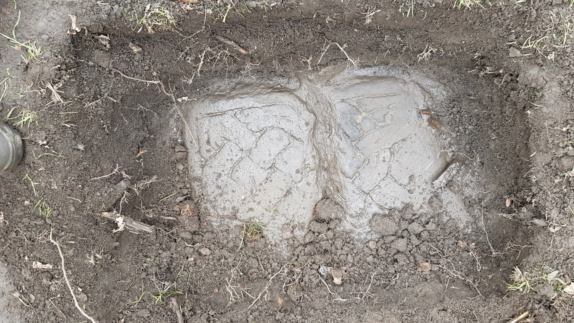 A Govan Stone emerges from the dirt.