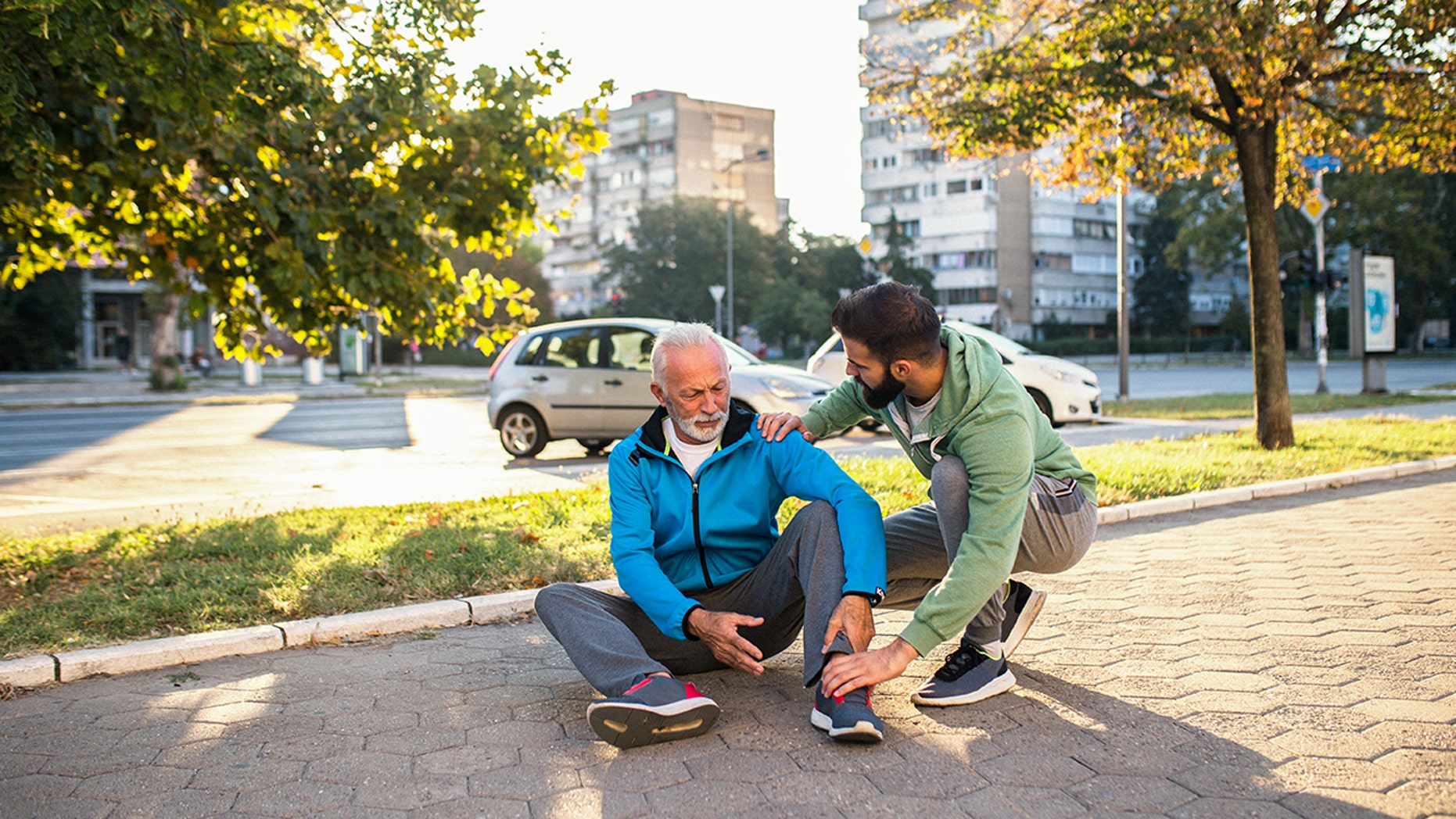 Son helping his father to stand up after his fall while jogging outdoors in city street.