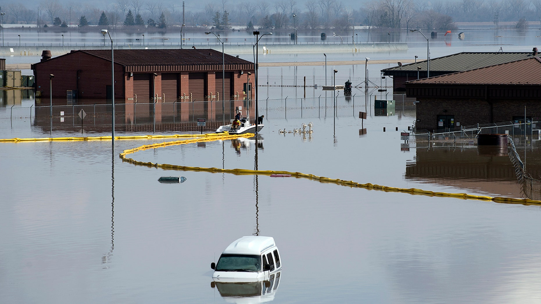 Environmental restoration employees deploy a containment boom from a boat on Offutt Air Force Base in Neb., as a precautionary measure for possible fuel leaks in the flooded area.