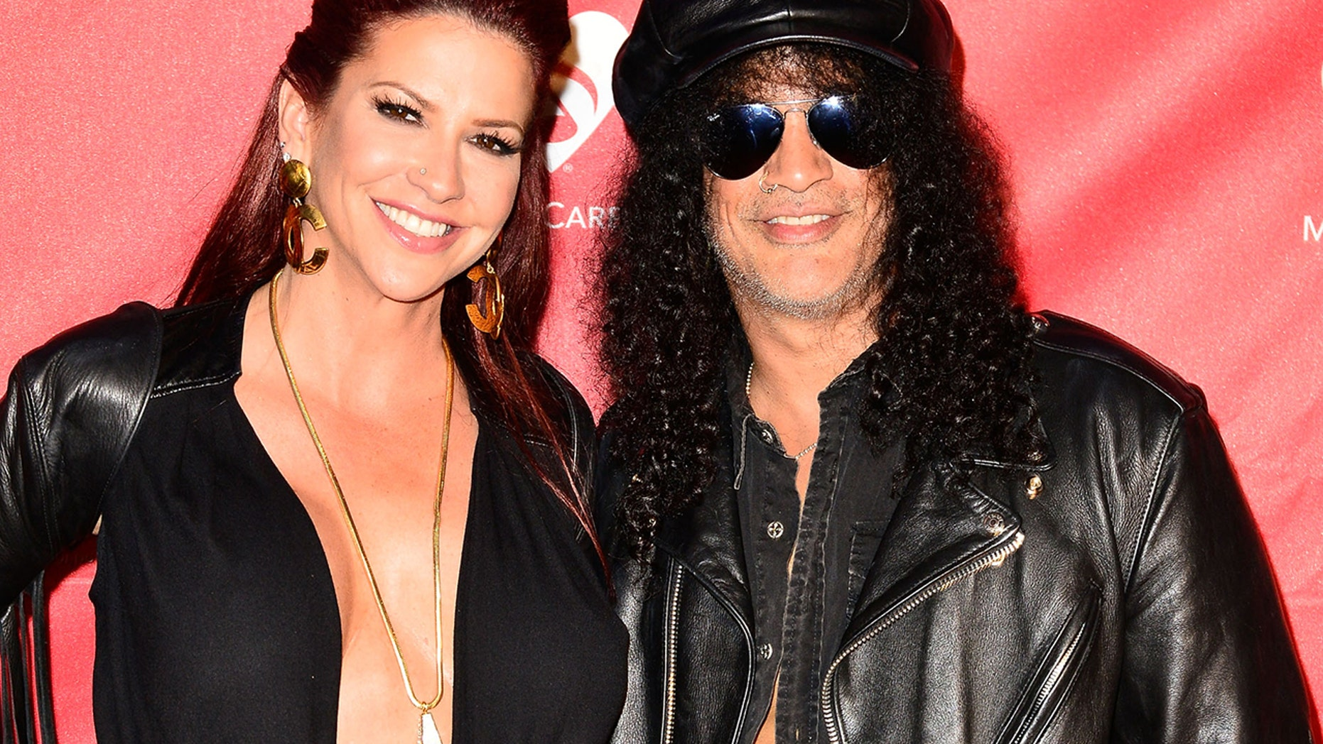 Musician Slash, right, and now-ex-wife Perla Hudson arrive at the MusiCares MAP Fund Benefit Concert at Club Nokia on May 12, 2014 in Los Angeles.