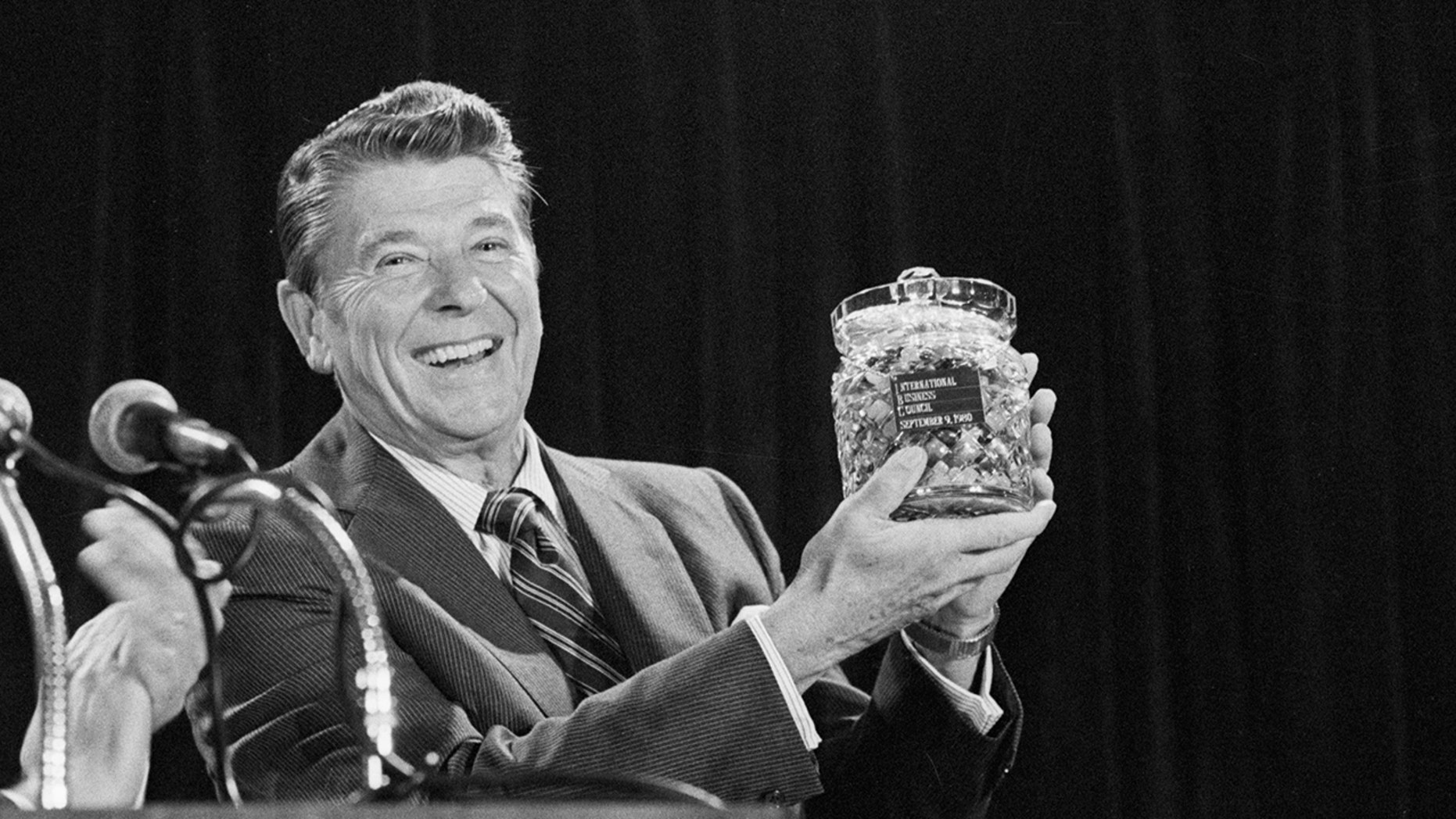 (Original Caption) 9/9/80 - Chicago, Illinois: Republican presidential candidate Ronald Reagan holds a crystal jar of jellybeans presented to him by Clyde Dicky, Jr., president of the International Business Council. (Getty)
