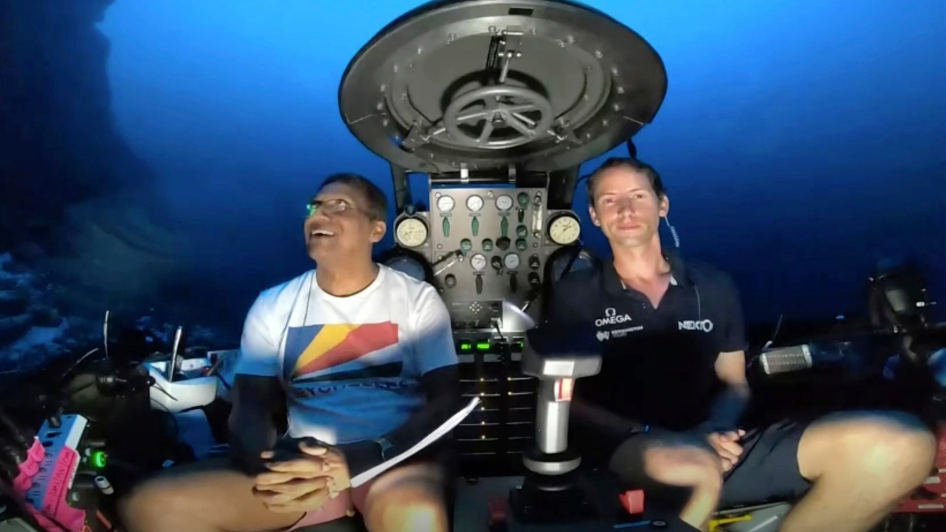 An image taken from video issued by Nekton shows Seychelles President Danny Faure, left, smiles after speaking from inside a submersible from the vessel Ocean Zephyr, under the water off the coast of Desroches, in the outer islands of Seychelles Sunday, April 14, 2019. (Nekton via AP)
