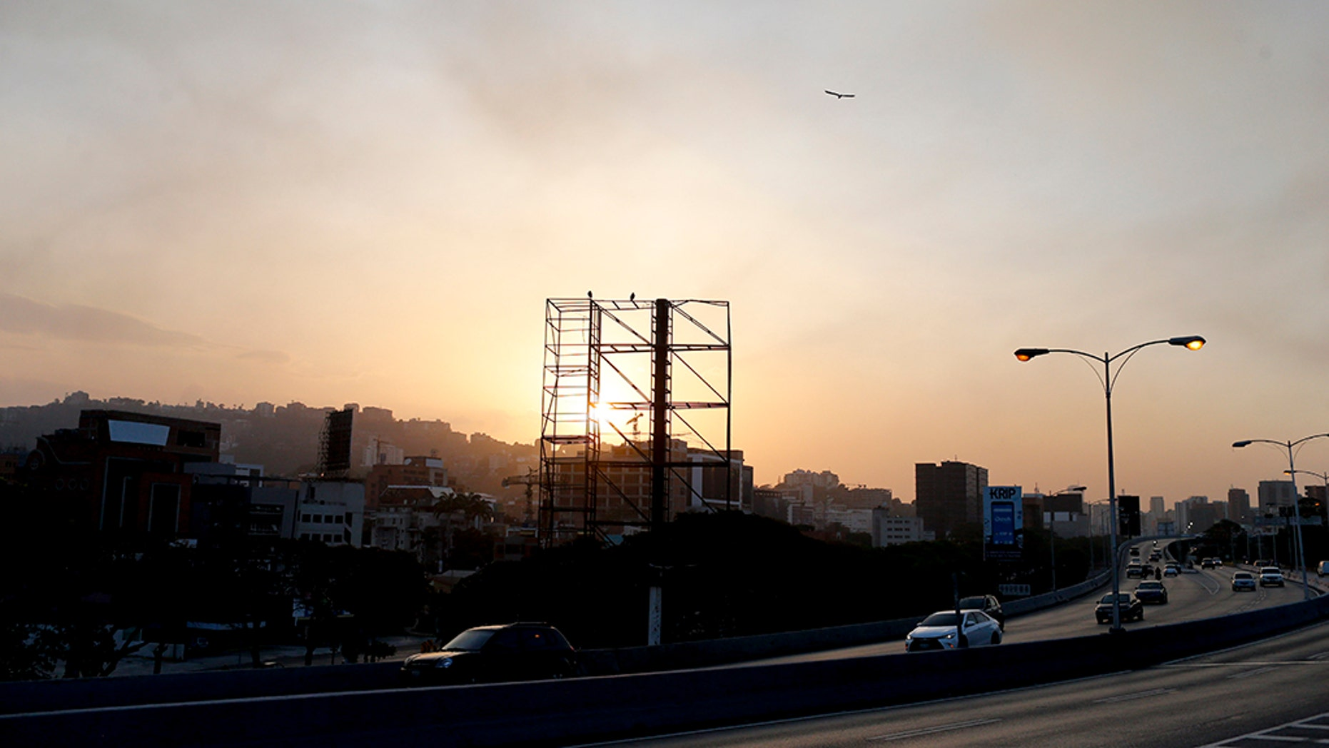 A billboard stands empty above a highway with no traffic as the sun sets in Caracas, Venezuela, Monday, March 18, 2019. When the sun goes down in Venezuela's capital, the once-thriving metropolis empties under darkness. (AP Photo/Natacha Pisarenko)