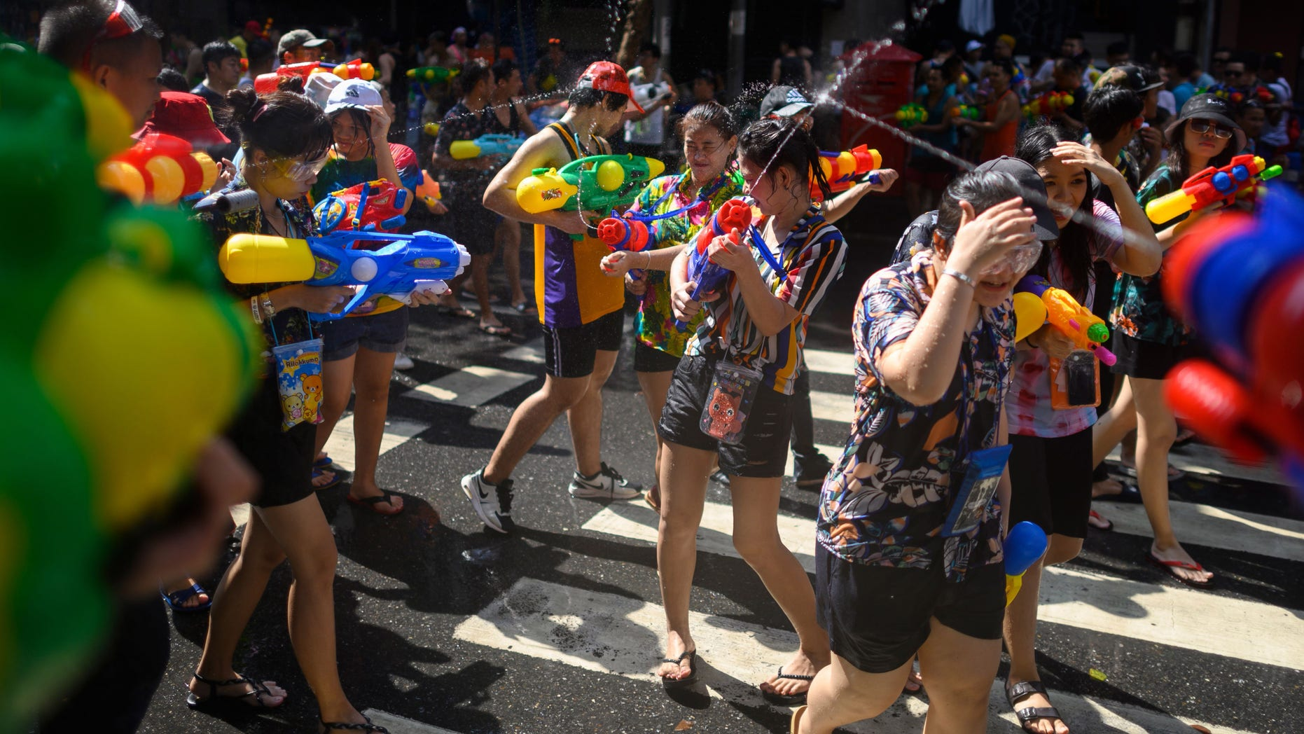 People use water guns to spray at one another as they celebrate the Buddhist New Year, locally known as Songkran, in Bangkok on April 14, 2019.