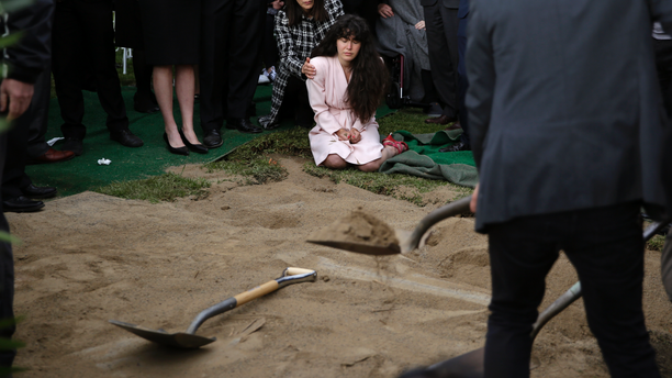 Hannah Kaye, center, the daughter of shooting victim Lori Kaye, sits on the ground with her aunt, Randi Grossman, as the last shovels of dirt cover her mother's grave during funeral services, Monday, April 29, 2019, in San Diego. Lori Kaye was killed when a man opened fire during Passover service on April 27 inside a synagogue near San Diego, as worshippers celebrated the last day of a major Jewish holiday. (AP Photo/Gregory Bull)