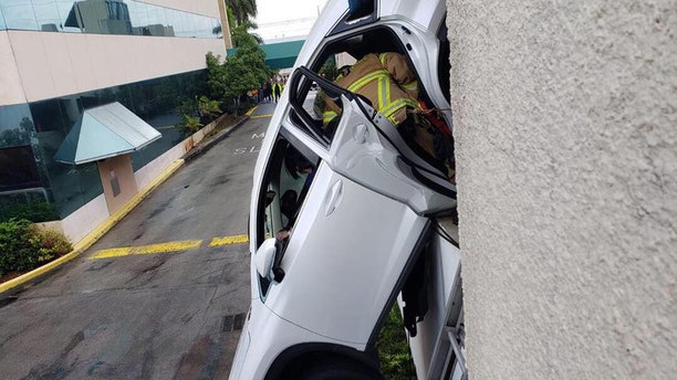 Authorities said the SUV was precariously hanging from the side of the parking garage.