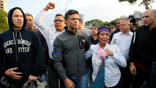 Opposition leader Leopoldo Lopez, center, is seen surrounded by supporters outside La Carlota air base in Caracas, Venezuela, Tuesday, April 30, 2019. Lopez, who had been under house arrest for leading an anti-government push in 2014, said he had been freed by soldiers and called for a military uprising.