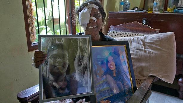 Anusha Kumari holds portraits of her daughter Sajini Venura Dulakshi and son Vimukthi Tharidu Appuhami, both victims of Easter Sunday's bomb blasts.