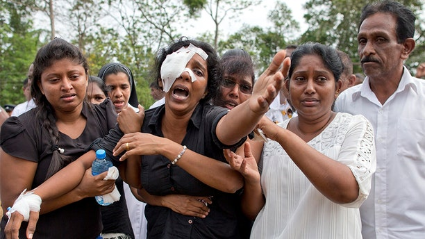 Anusha Kumari, second from left, weeps during a mass burial for her husband, two children and three siblings, all victims of Easter Sunday's bomb attacks, in Negombo, Sri Lanka.